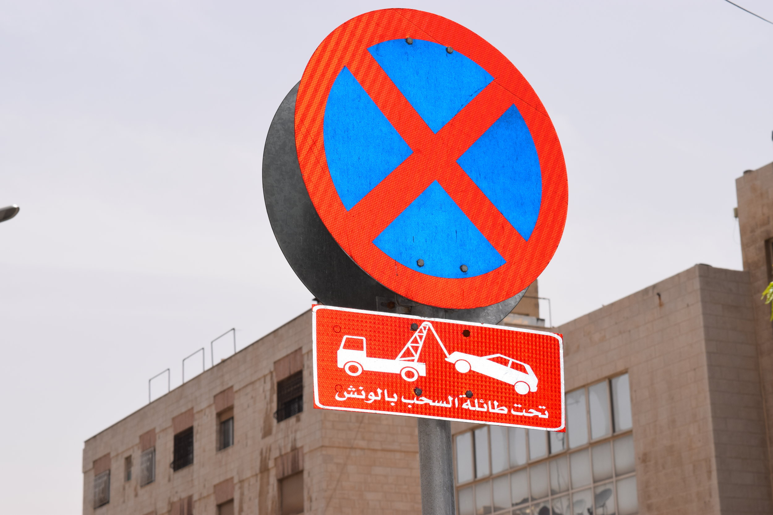 1. A warning sign indicating that cars parked in the no-parking zone will be towed.