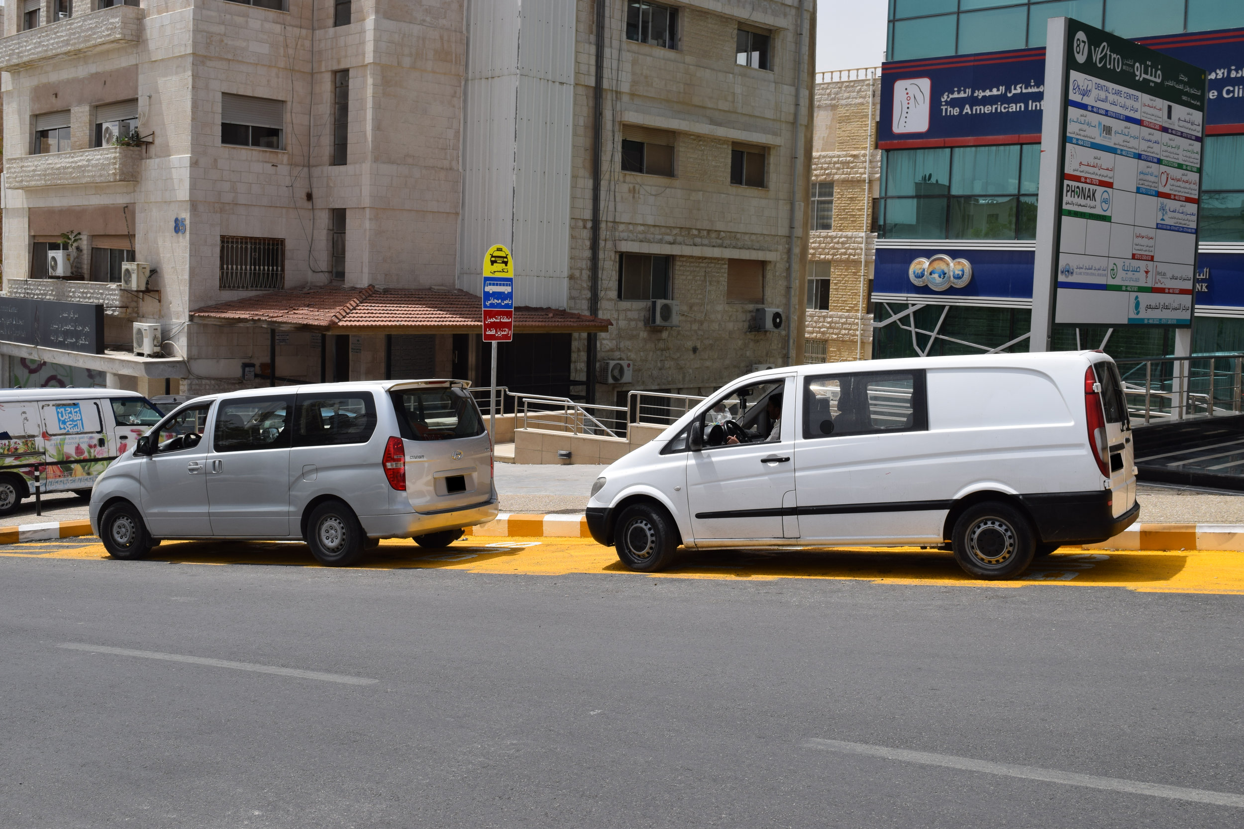 Two vans parked in a taxi parking zone.