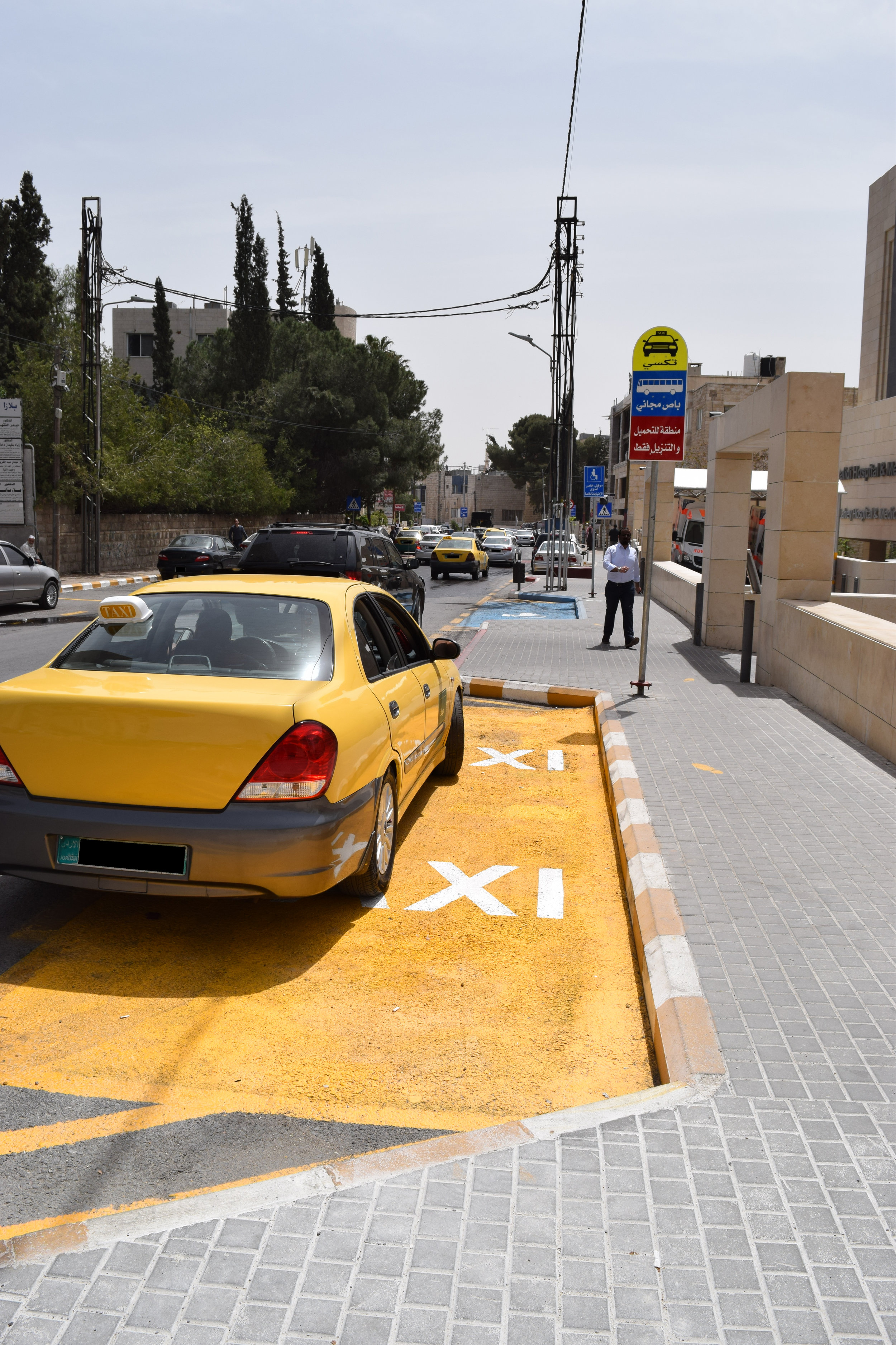A taxi parked in a taxi parking zone, but a part of the car juts out into the street.