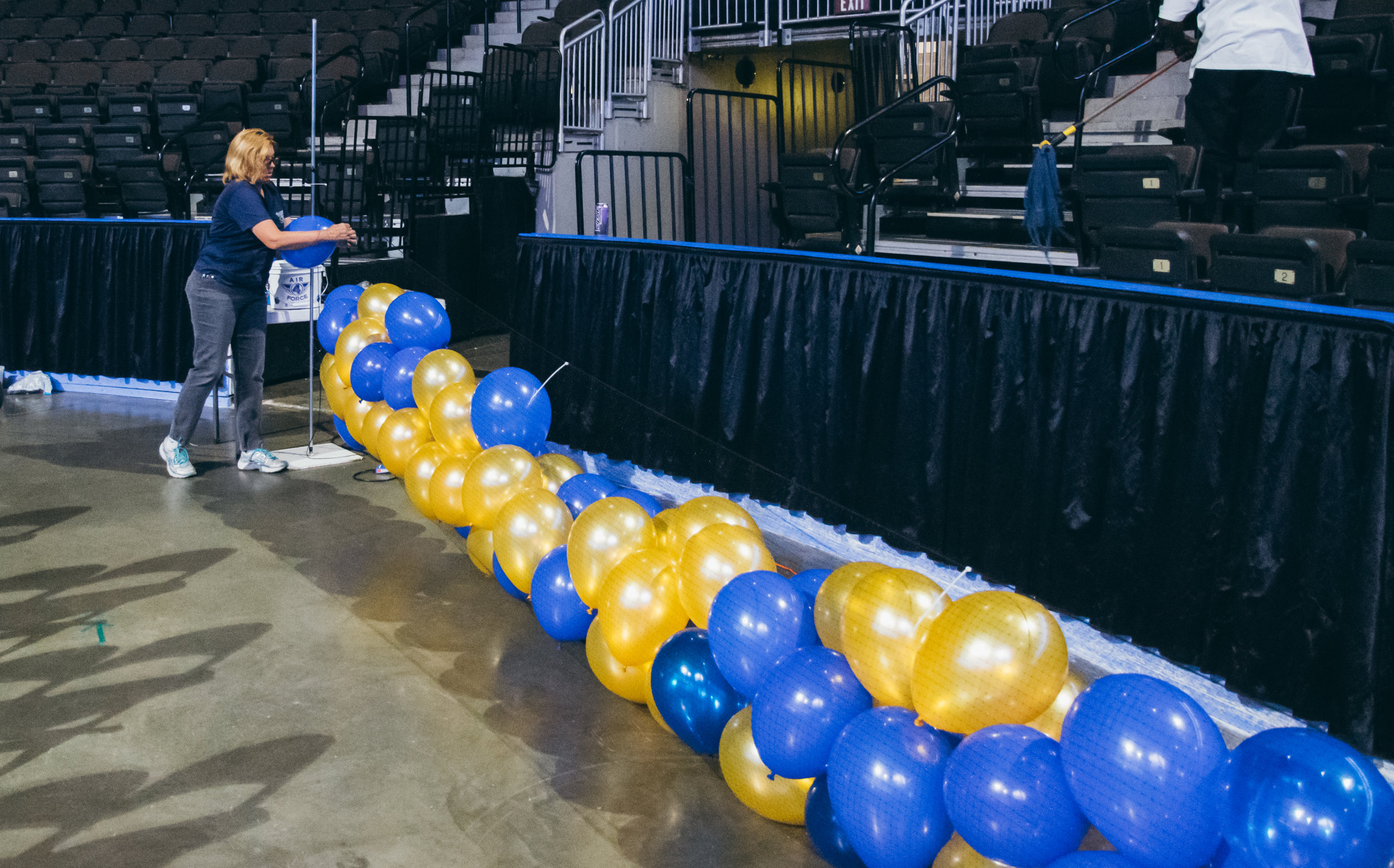 Balloons for the drop are inflated and set into a light net, to be lifted up to the rafters of the arena.