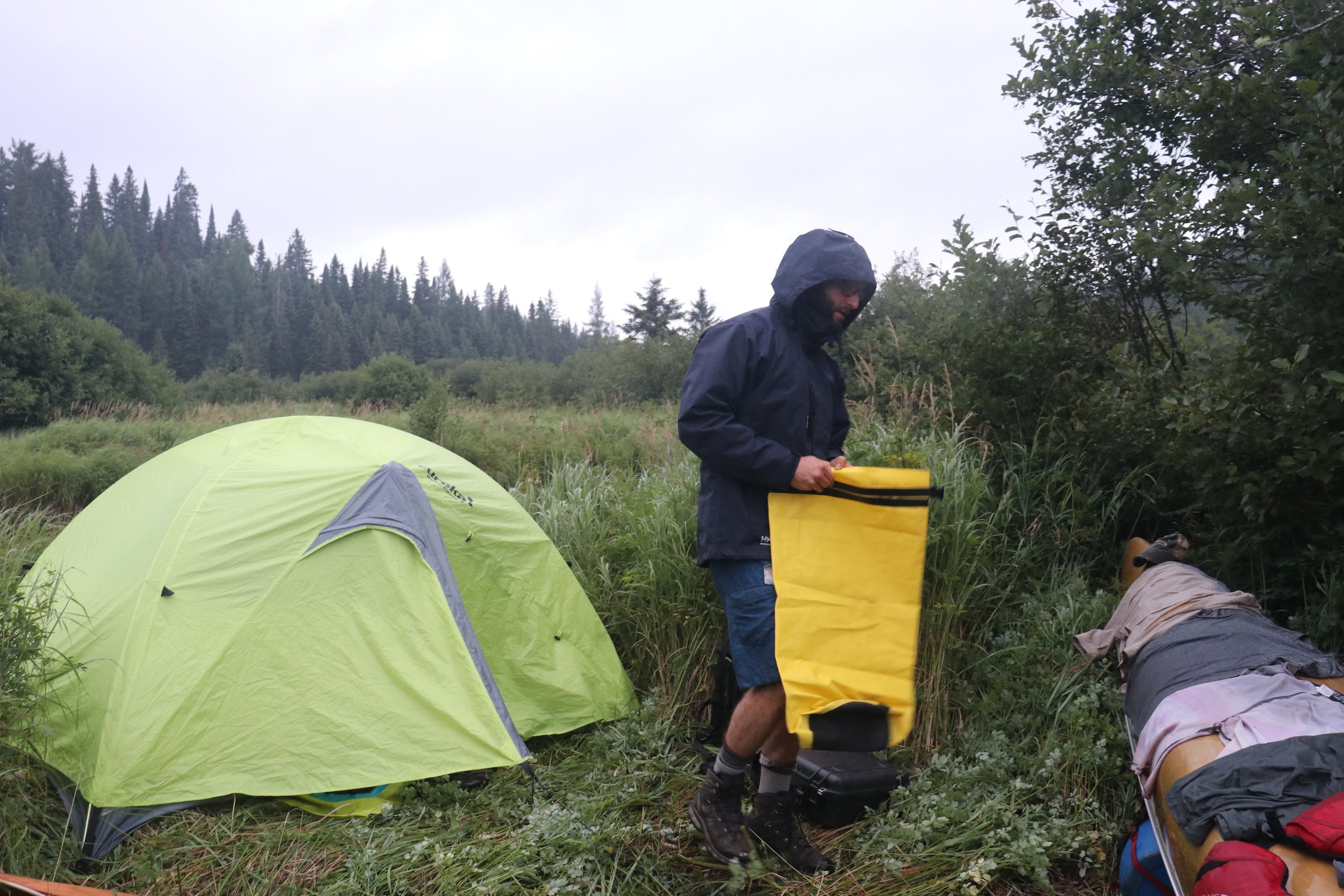 We were soaked from the alders, the temp had dropped, there was no more daylight, and we had no idea where we were. Forced to camp on a grass patch along the river.