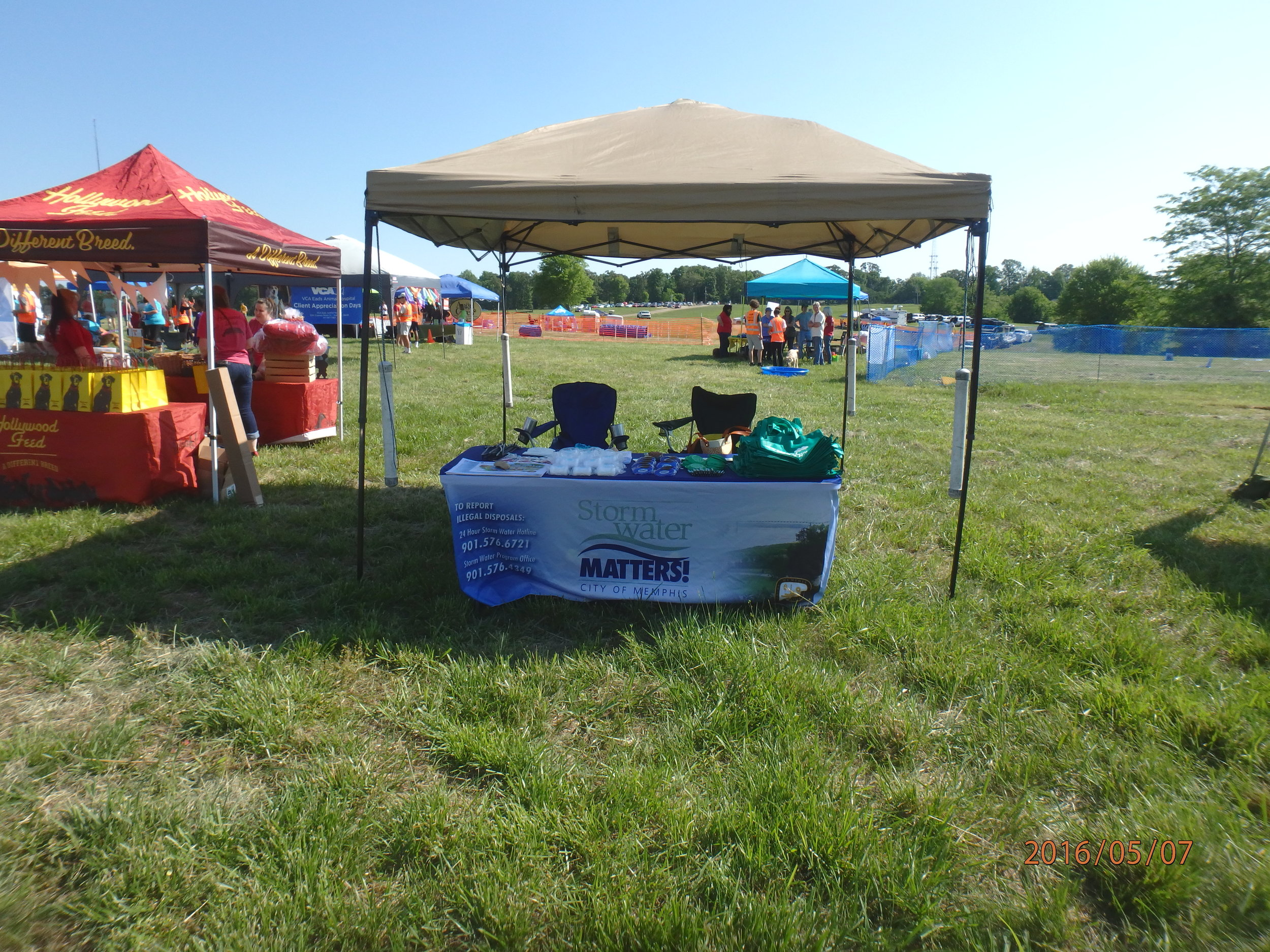 Our 2016 Dog-A-Roo booth. We provide many useful items to promote proper pick-up and disposal of pet waste, such as pet waste pick-up bag dispensers and Scoop-the-Poop yard signs. The bacteria in pet waste is a storm water contaminant.
