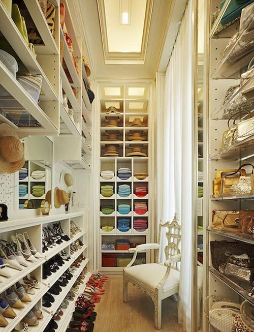 This dreamy walk in closet is on the smaller side but so warm and inviting. It's organized to a T and we love the little custom hat compartments!