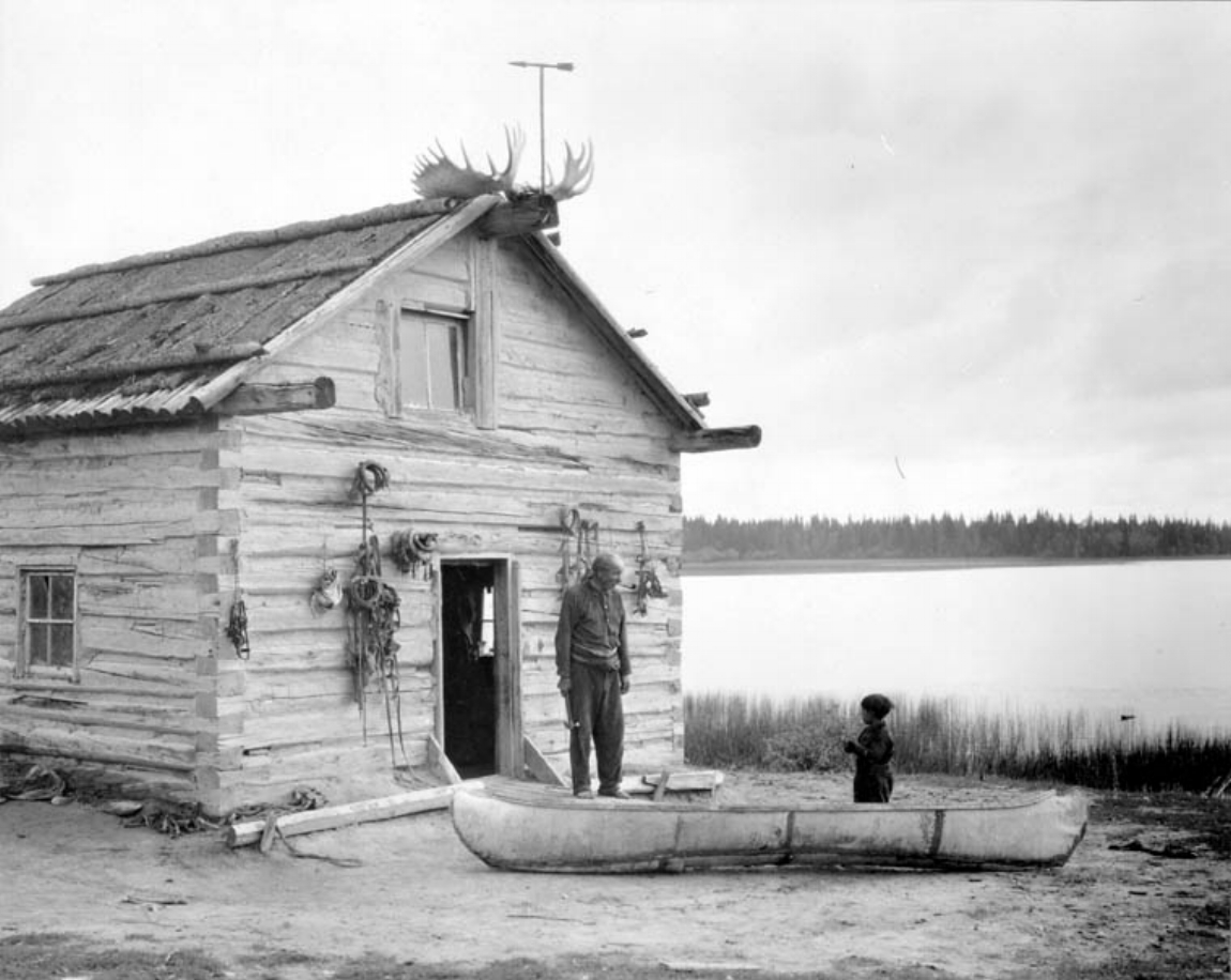 Image 3: Louis Vallee and his grandson Baptiste in front of his shack. Pelican Lake, Prince Albert National Park. Canada. Dept. of Interior / Library and Archives Canada / PA-049784.