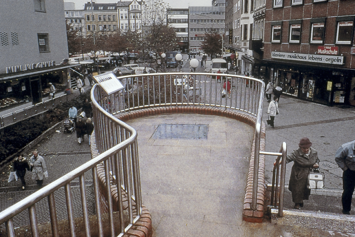 Esther Shalev-Gerz and Jochen Gerz, Monument Against Fascism (1986), permanent installation, Hamburg, Germany, installation view, 1993. The panel at left includes documentation of the column at various stages of its descent and the artists' invitation, in seven languages, for people to write on and inscribe the monument. Photograph courtesy of Esther Shalev-Gerz