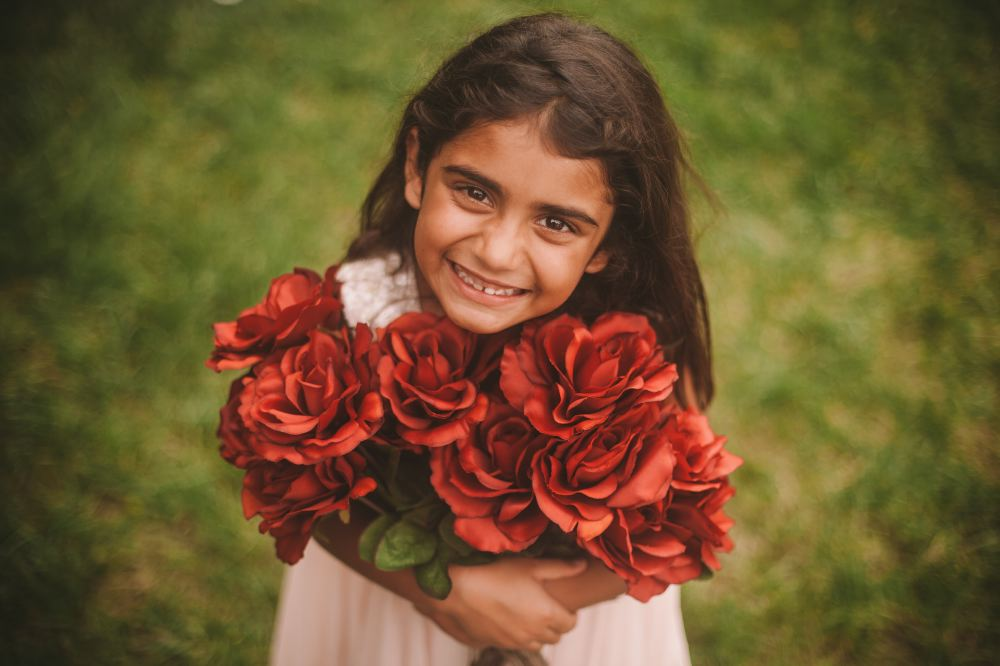 san   diego wedding photographer | child looking up while holding a lot of red   flowers