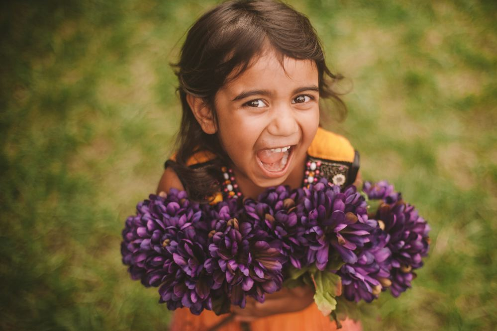san   diego wedding photographer | child smiling while holding lavenders in her   arms