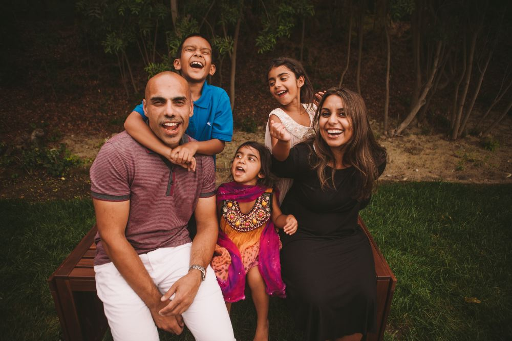 san   diego wedding photographer | man and woman smiling with 3 kids sitting on a   bench