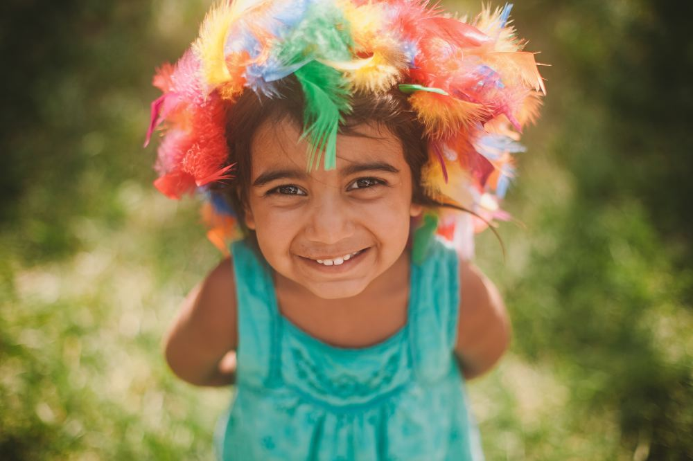 san   diego wedding photographer | kid in teal dress with feathers on head smiling   at camera