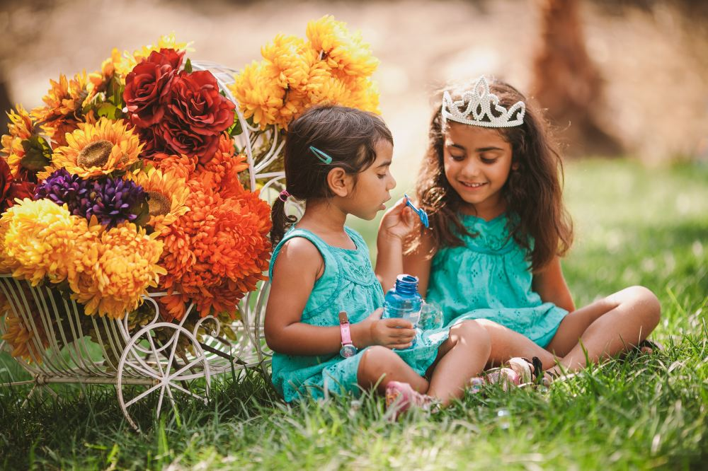san   diego wedding photographer | children in teal dresses in front of flower   casing