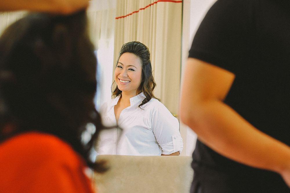 san   diego wedding photographer | woman in white shirt smiling at mirror