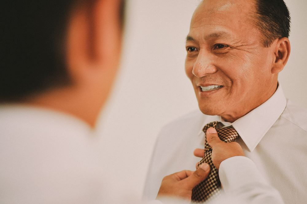 san   diego wedding photographer | middle aged man being helped with his gold tie
