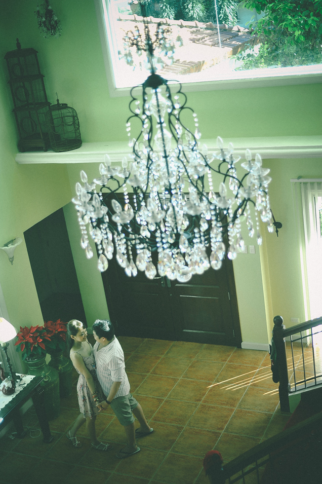 san   diego wedding photographer   shot of man and woman standing in middle of room   under chandelier