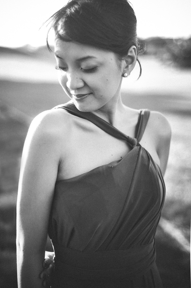 san   diego wedding photographer   woman in dress and pearl earrings posing smiling   looking down with eyes closed