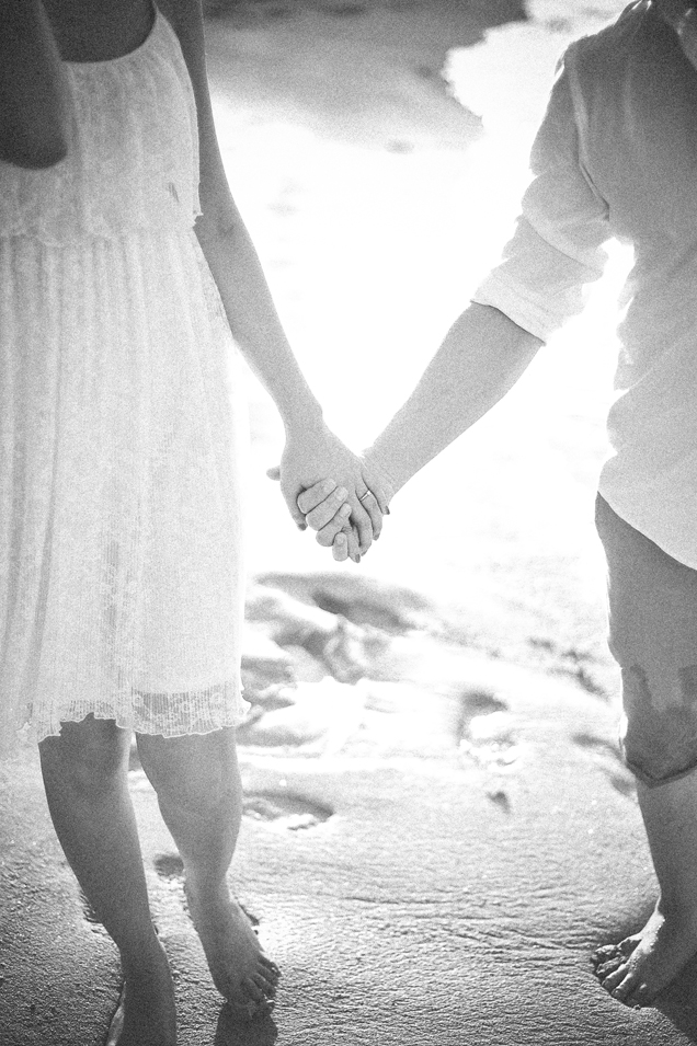 san   diego wedding photographer   monotone shot of man and woman holding hands on   beach shore