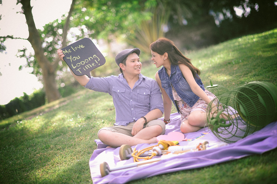 san   diego wedding photographer   man holding up sign while sitting down with   woman