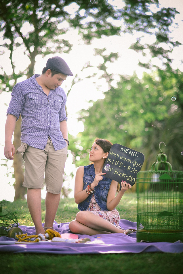 san   diego wedding photographer   man standing with woman sitting holding sign   with prices