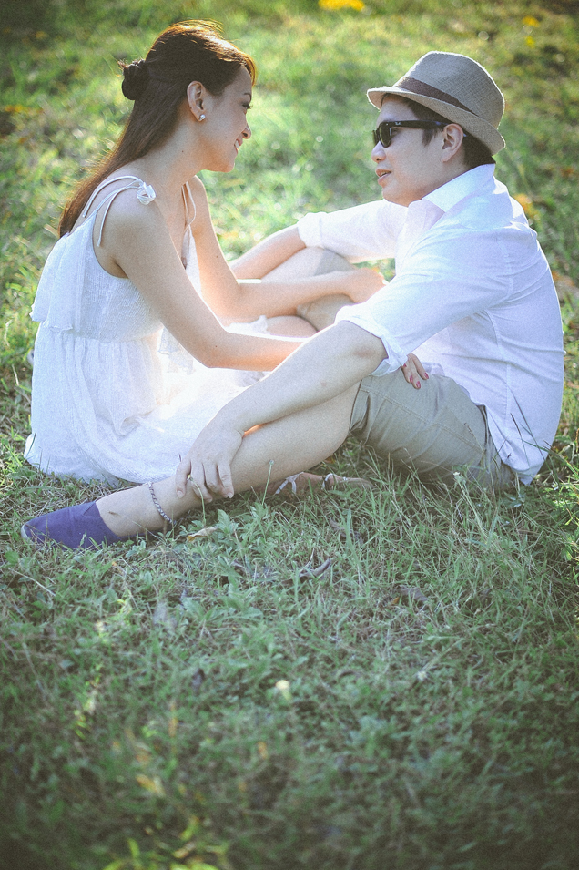 san   diego wedding photographer   man in fedora and shades sitting with woman in   white sundress