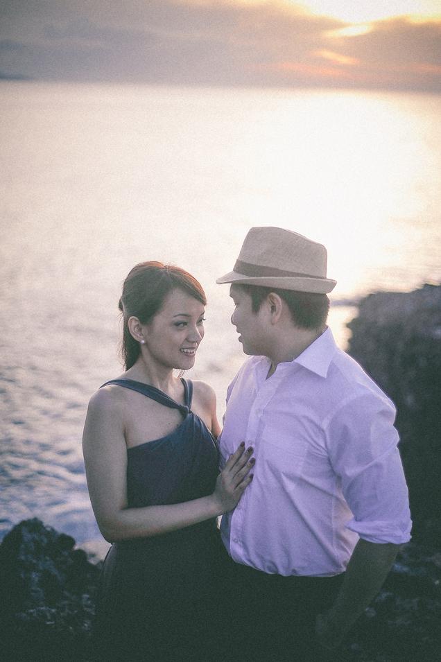 san   diego wedding photographer   man in fedora looking at woman in dress on top   of rocky shore