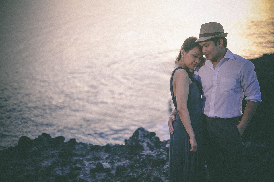 san   diego wedding photographer   man in fedora holding woman in dress close on   top of rocky shore