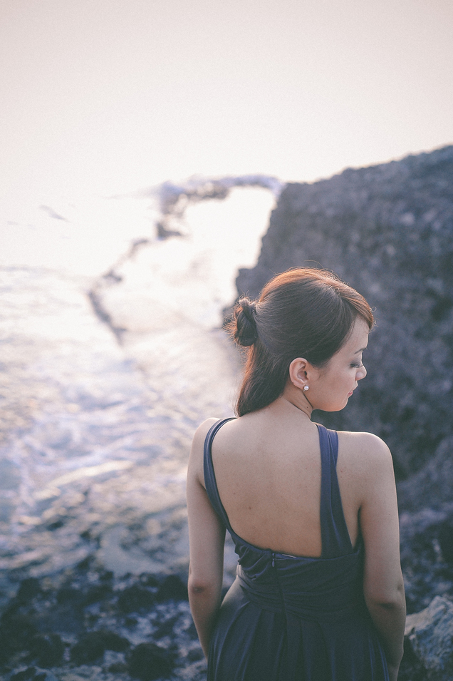 san   diego wedding photographer   woman with back facing the camera on top of   rocky shore