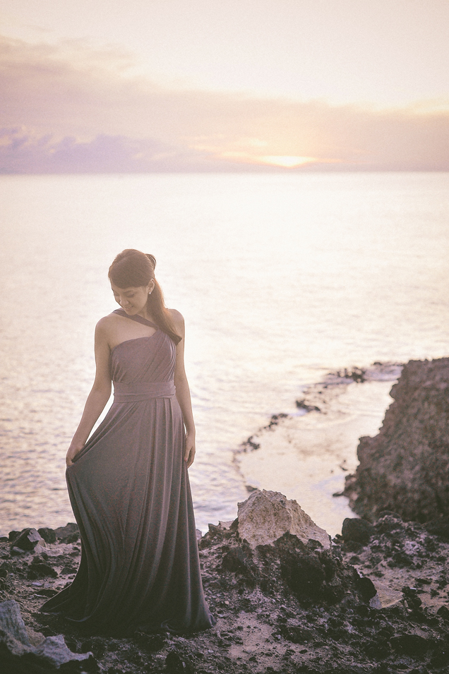san   diego wedding photographer   woman in dress posing by rocky shore in sunset