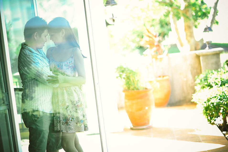 san   diego wedding photographer   man and woman holding each other seen through   glass window with potted plants outside
