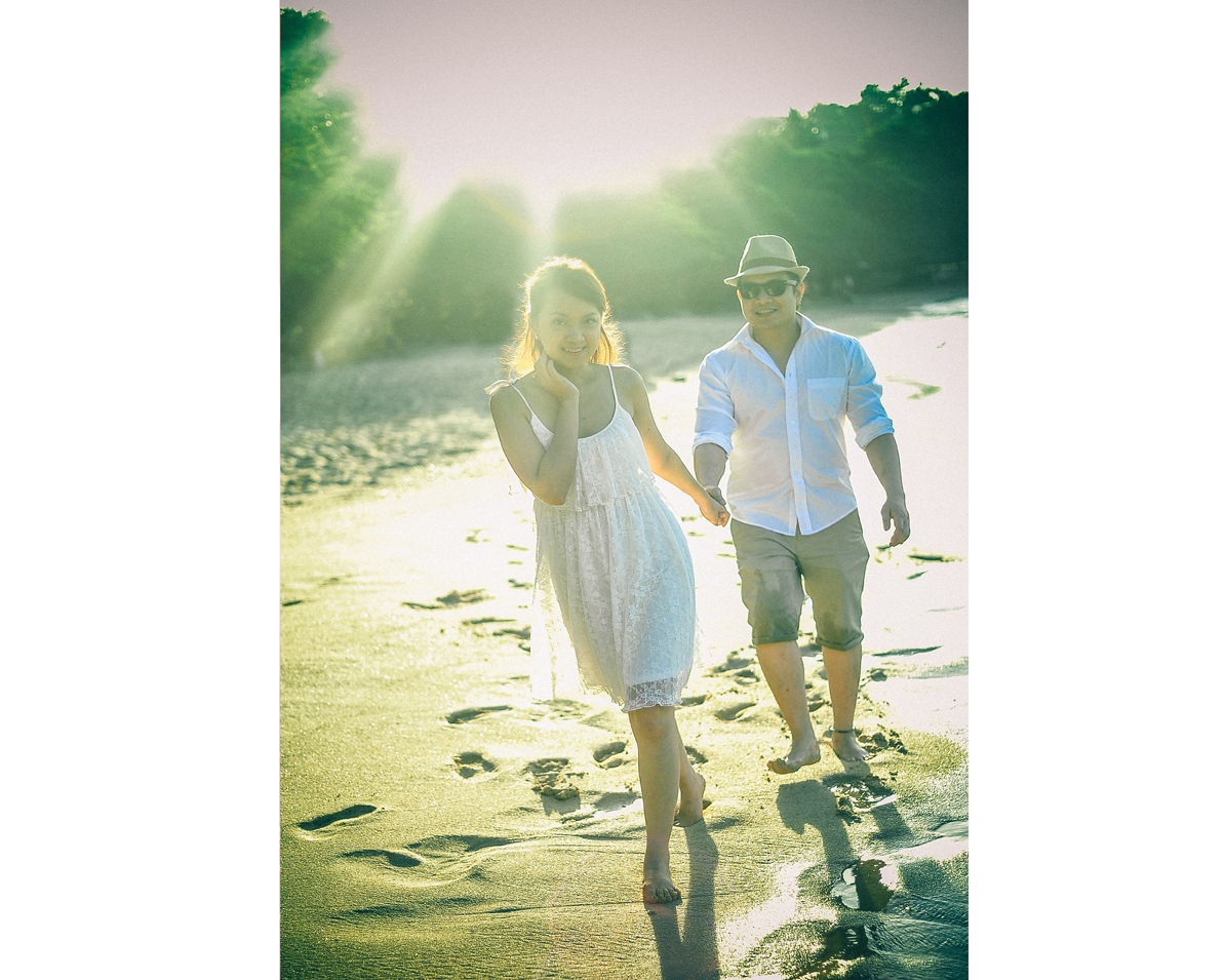 san   diego wedding photographer   woman walking with man behind her holding her   hand on beach shore exposed by sunlight