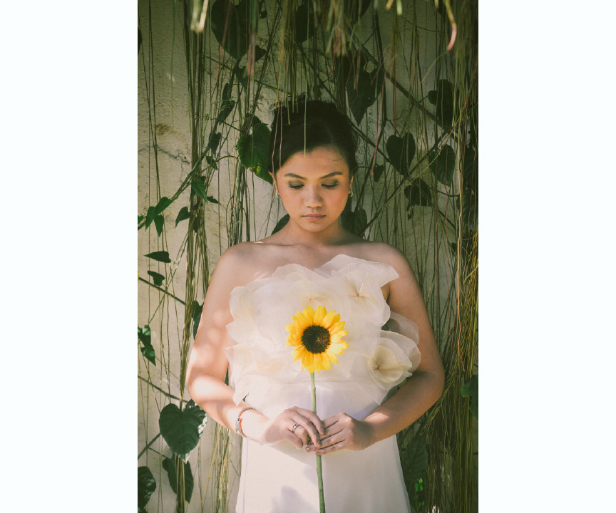 san   diego wedding photographer | woman in white dress with sunflower standing in   front of wall with vines