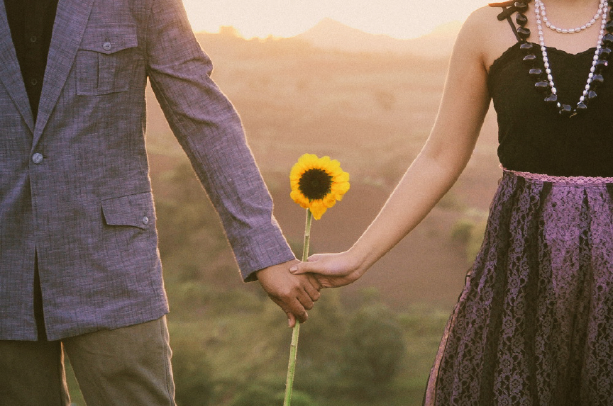 san   diego wedding photographer | man and woman holding hands with sunflower   between them