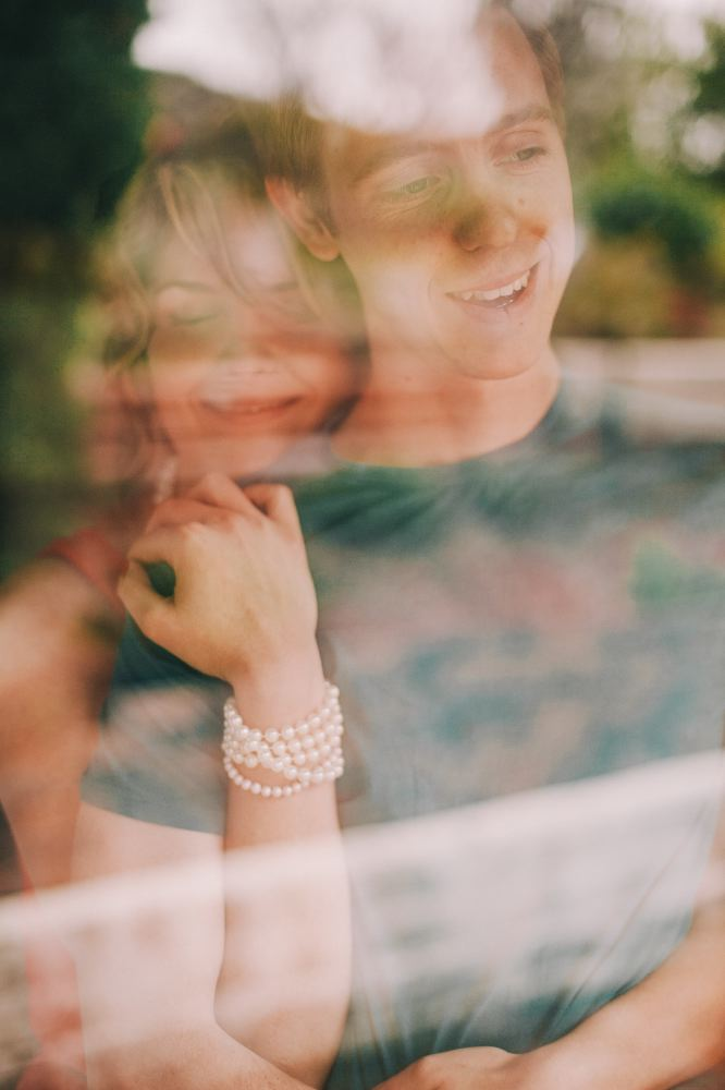 san   diego wedding photographer | woman hugging man from behind glass window   reflecting trees