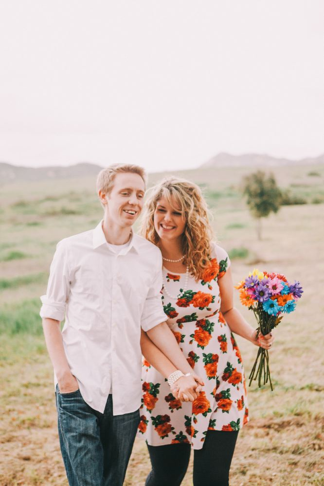 san   diego wedding photographer | man in white shirt and jeans holding hands with   woman in white floral dress