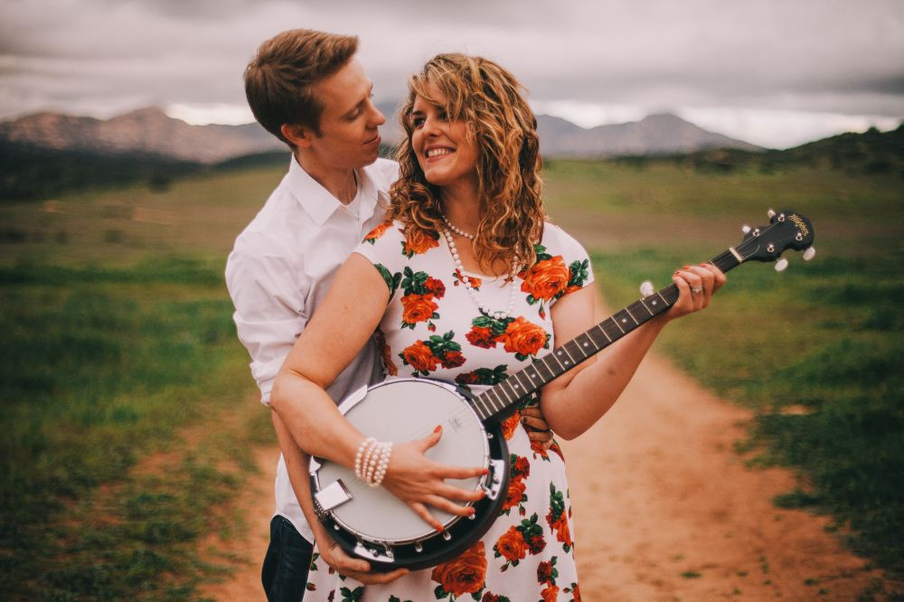 san   diego wedding photographer | woman holding banjo with man hugging her from   behind