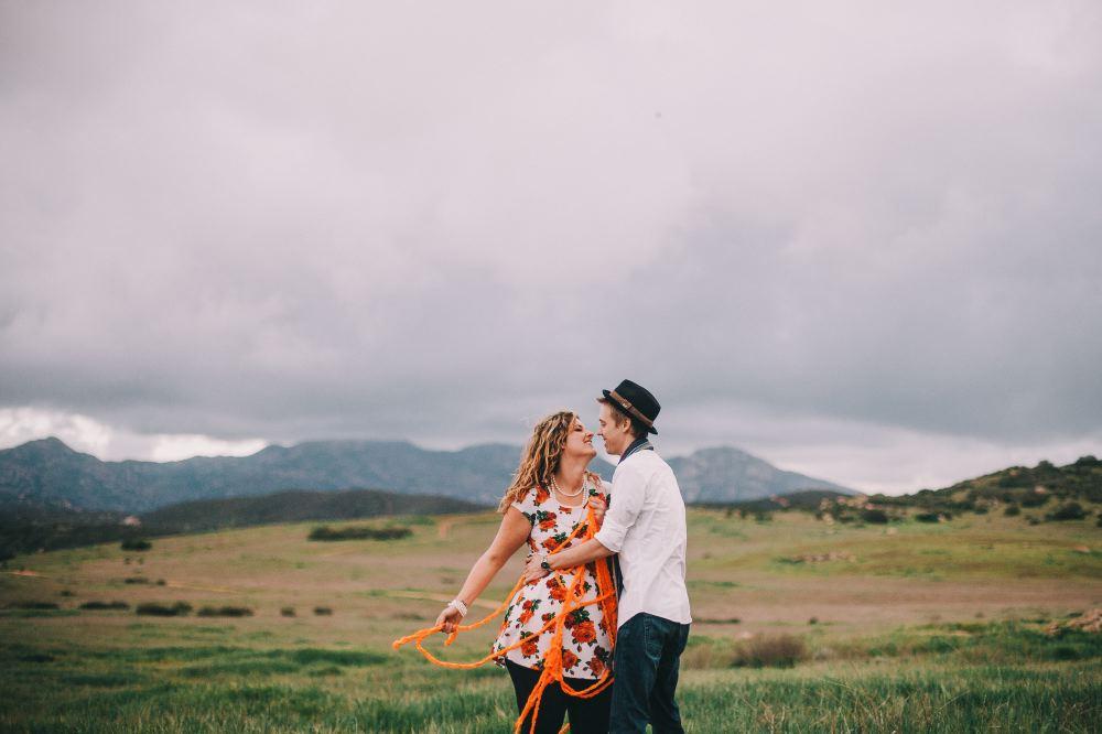 san   diego wedding photographer | man with arm around woman's waist with orange   yarn wrapped around her