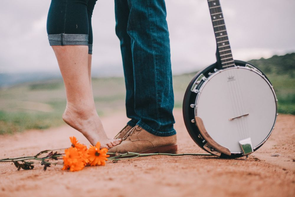 san   diego wedding photographer | woman tiptoeing on man's feet with banjo on   floor