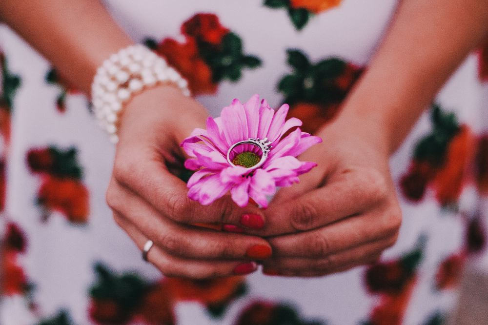 san   diego wedding photographer | woman holding pink flower with ring on it