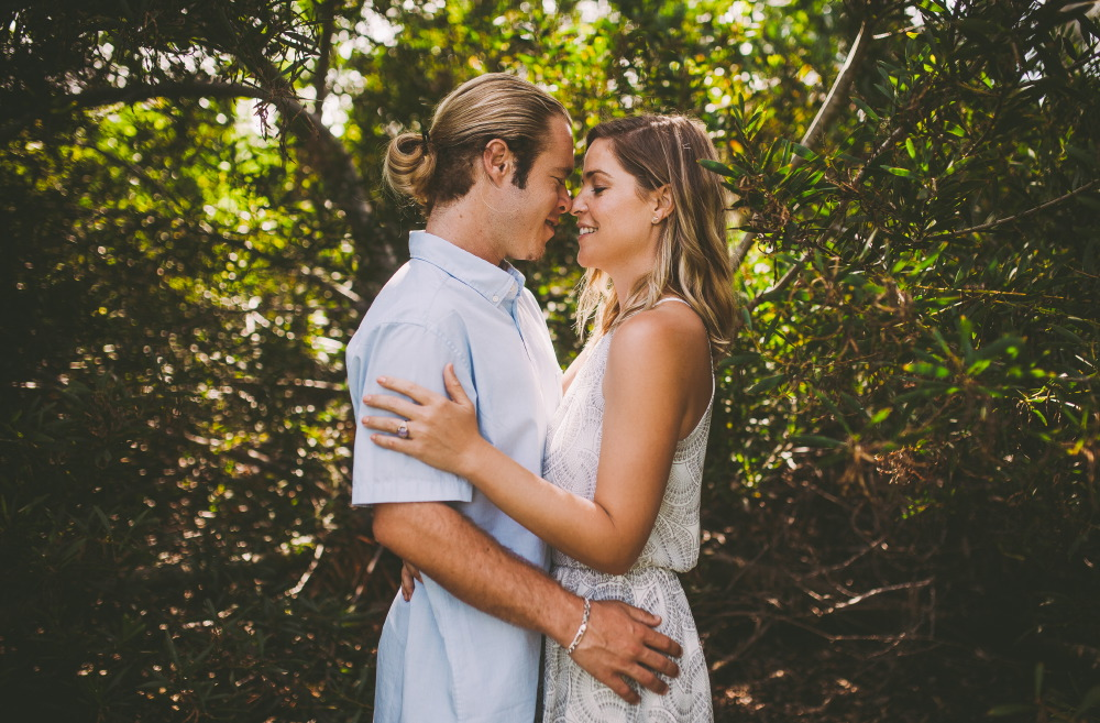 san   diego wedding photographer | blonde man in ponytail with hand on blonde   woman's waist facing each other and with noses together