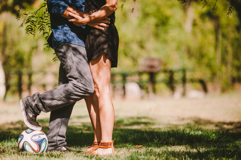 san   diego wedding photographer | bottom half shot of man in dark blue polo   stepping on soccer ball and hugging woman in black dress