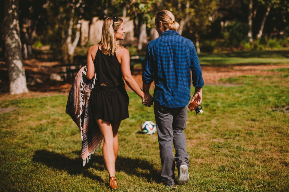 san   diego wedding photographer | blonde woman holding blanket holding hands with   blonde man in ponytail with soccer ball in background