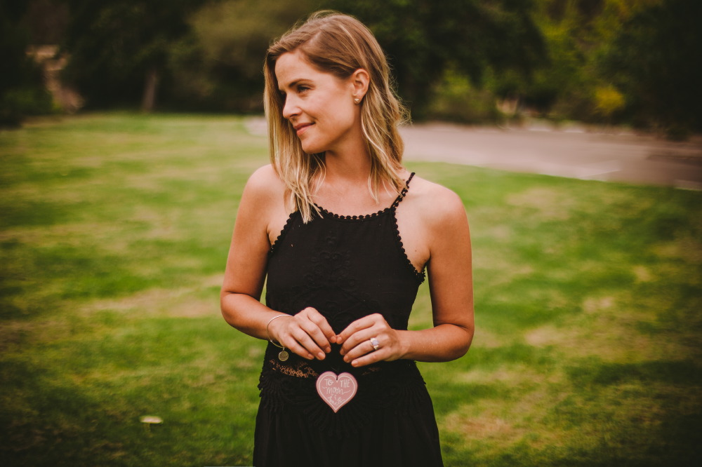 san   diego wedding photographer | blonde woman in black dress looking to side and   holding heart-shaped note