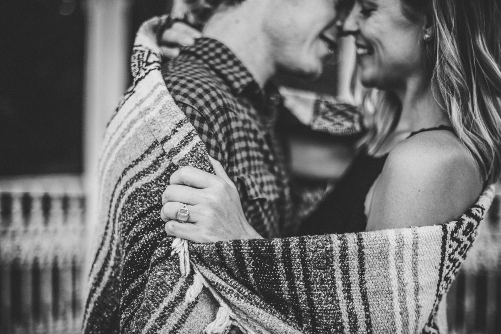san   diego wedding photographer | monotone shot of blonde woman and man in   checkered polo covered in blanket and about to kiss