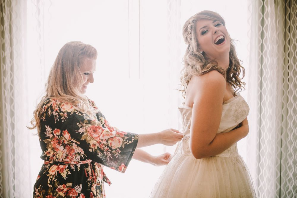 san   diego wedding photographer | bride laughing being helped put on wedding dress