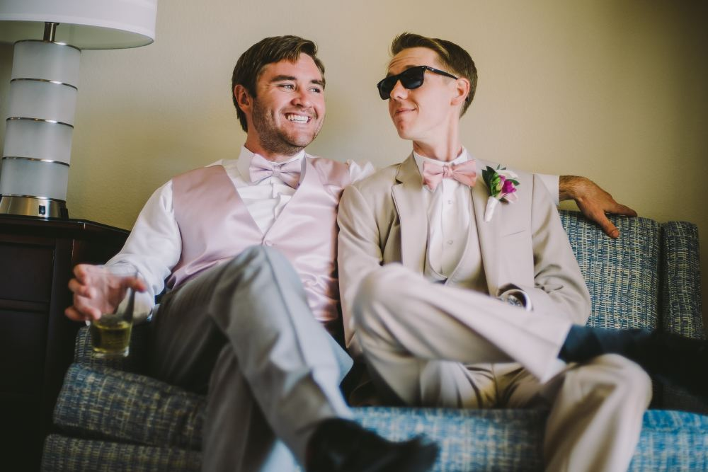 san   diego wedding photographer | men in grey formal suits sitting on blue couch
