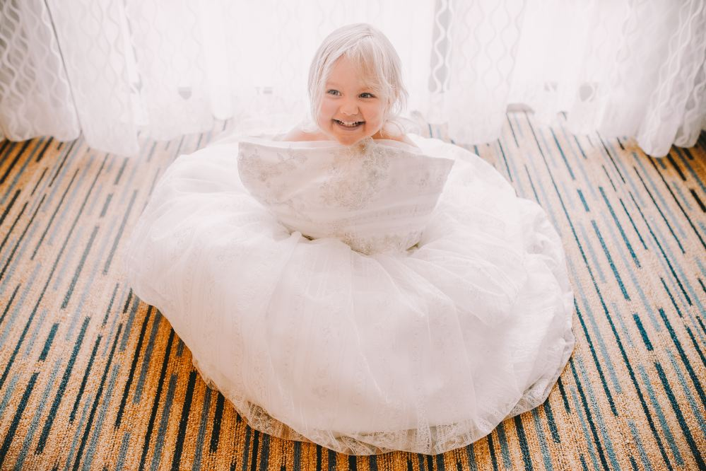 san   diego wedding photographer | child in white floofy dress sitting and smiling