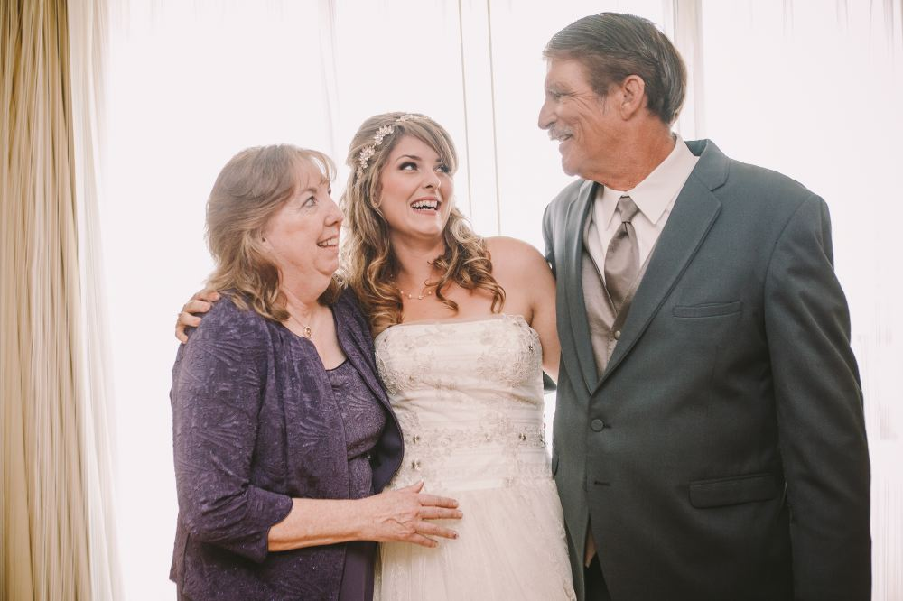 san   diego wedding photographer | bride to be posing with arms around two middle   aged people