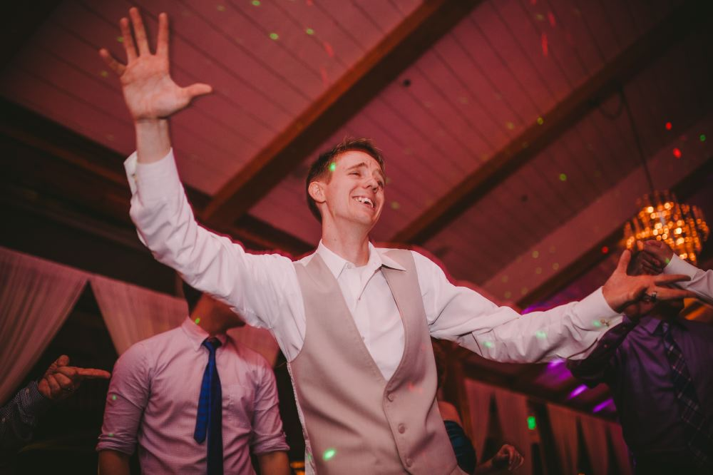 san   diego wedding photographer | man in beige vest dancing smiling with arms out
