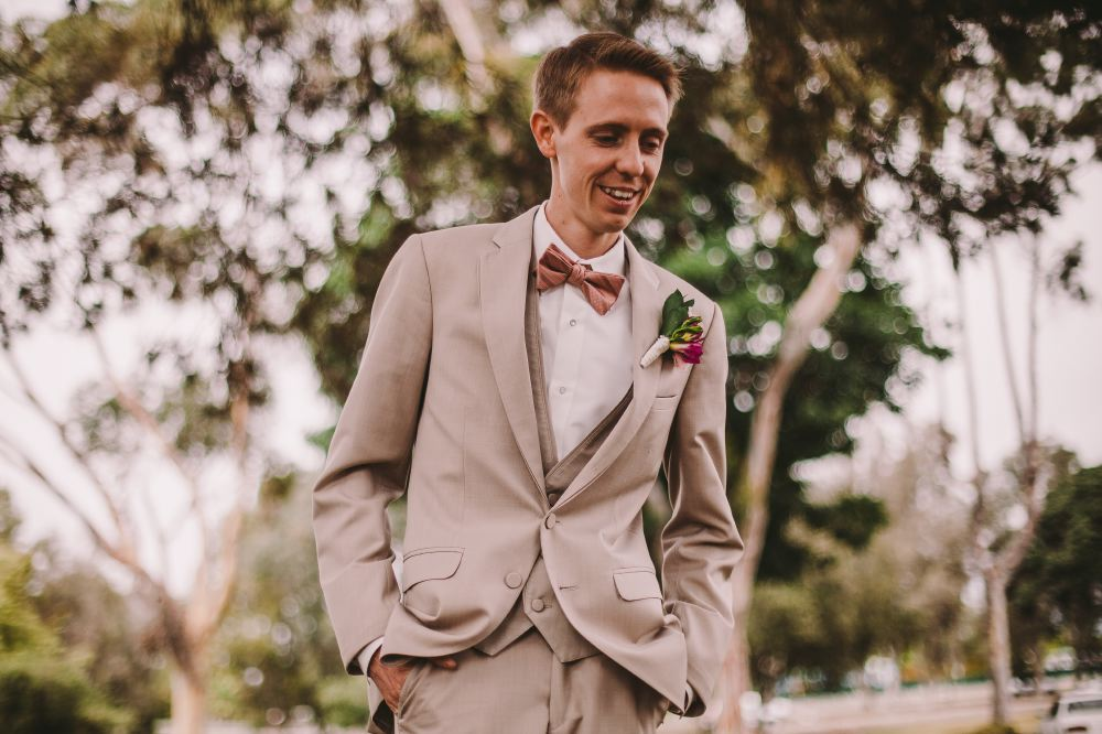 san   diego wedding photographer | groom in grey suit and pink bow tie walking   smiling