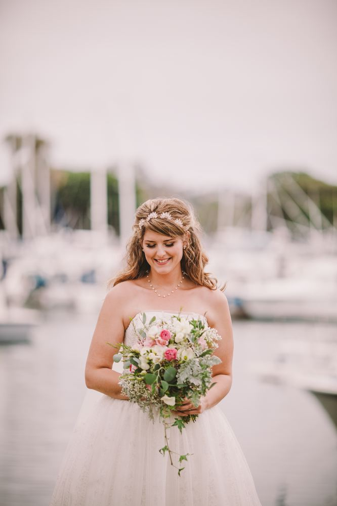 san   diego wedding photographer | bride smiling down at bouquet of flowers with   docks behind her