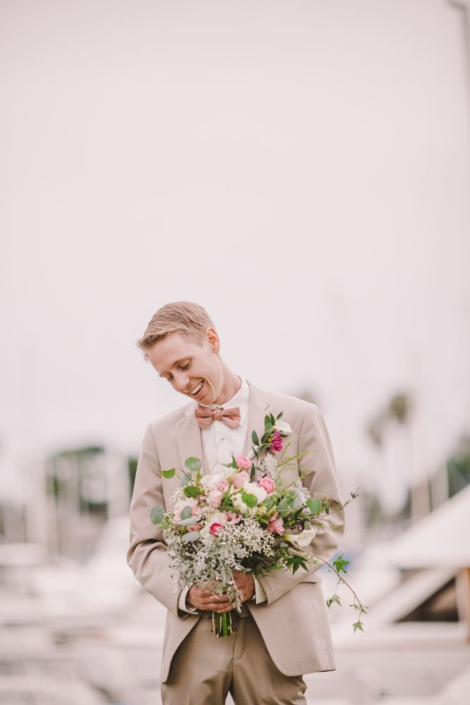 san   diego wedding photographer | groom holding bouquet of flowers with docks   behind him