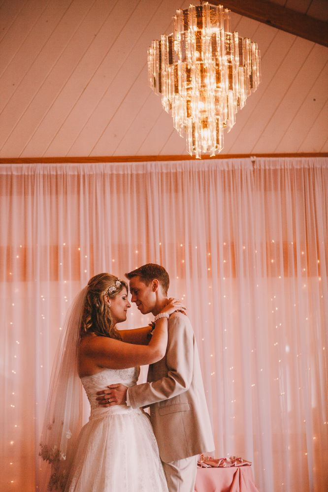 san   diego wedding photographer | bride and groom in pink room dancing under   chandelier